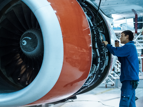 Man working on aeroplane engine