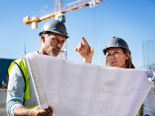 Male and female construction workers looking at plans